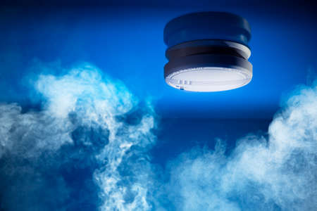smoke detector on a blue background 스톡 콘텐츠