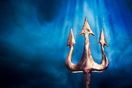 Poseidons trident on a dark sky background Stock Photo