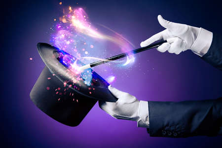 tricks: Magician hand with magic wand and hat Stock Photo