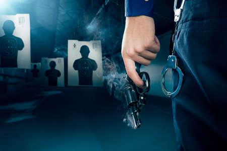 tiro al blanco: El oficial de policía con una pistola en un campo de tiro