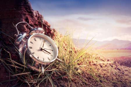 ahorros: reloj de alarma que se sienta en la hierba al atardecer o amanecer Foto de archivo