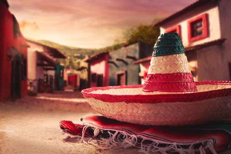 """chapeau paille: Chapeau mexicain """"sombrero"""" sur un """"sarape"""" dans une ville mexicaine au coucher du soleil"""