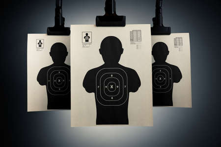 pistola: Disparos blancos que cuelgan sobre un fondo gris Foto de archivo