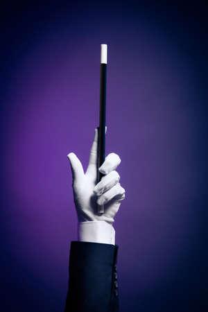 Magician hand with magic wand