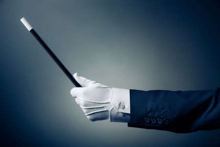 tricks: Magician hand with magic wand