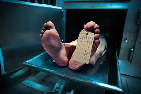 Grungy photo of feet with toe tag on a morgue table