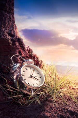 alarm clock sitting on the grass at sunset or sunrise