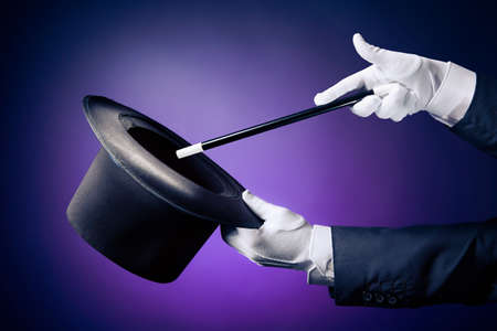 Magician hand with magic wand and hat Stock Photo
