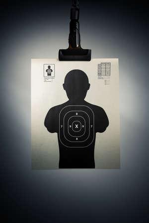 Obiettivo della fucilazione appeso su uno sfondo grigio Archivio Fotografico