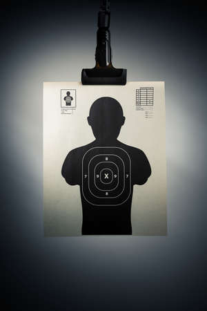 Shooting target hanging on a grey background