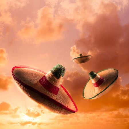 traje mexicano: imagen de formato cuadrado de sombreros mexicanos en un cielo anaranjado dramático Foto de archivo