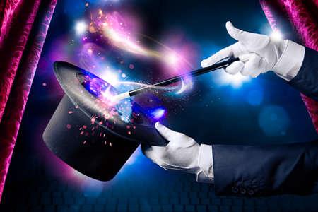 alzando la mano: La mano del mago con la varita y el sombrero mágico Foto de archivo