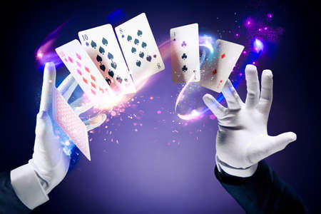 tricks: Magician hands with magic cards Stock Photo