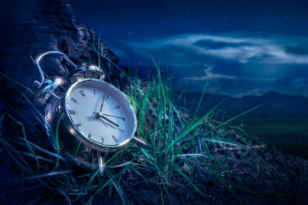 alarm clock sitting in the grass at night