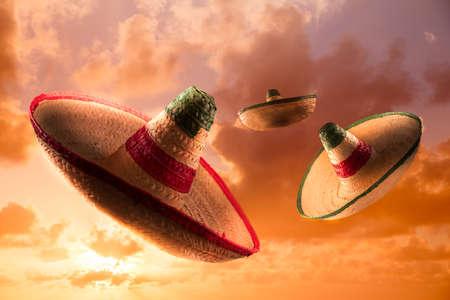 traje mexicano: Sombreros mexicanos en un cielo de color naranja dramática