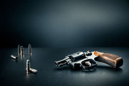 firearms: gun sitting on a table with bullet shells