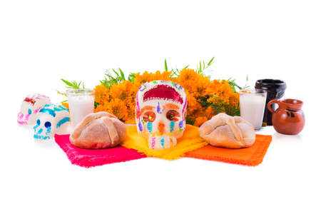 sugar skull used for dia de los muertos celebration isolated on white with cempasuchil flowers Stock Photo