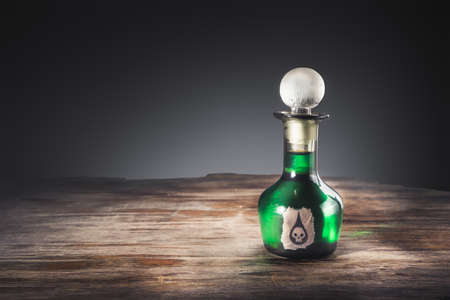 high contrast image of a poison bottle on a wooden surface Archivio Fotografico