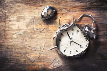 destroyed alarm clock on a wooden background Stock Photo - 64138835