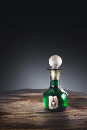 poison bottle: high contrast image of a poison bottle on a wooden surface Stock Photo