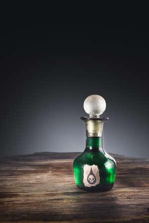 poison bottle: high contrast image of a poison bottle on a wooden surface Foto de archivo