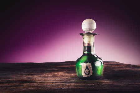veneno frasco: high contrast image of a poison bottle on a wooden surface Foto de archivo