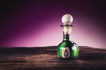 veneno frasco: imagen de alto contraste de una botella de veneno en una superficie de madera