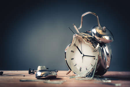 destroyed alarm clock on a wooden background