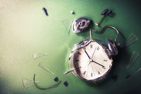 Destroyed alarm clock on a chalkboard / late for school concept