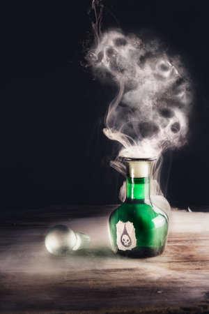 veneno frasco: botella de veneno en una superficie de madera con cráneos hecha de humo