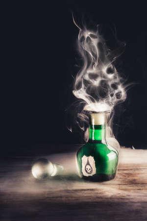 poison bottle: botella de veneno en una superficie de madera con cr�neos hecha de humo