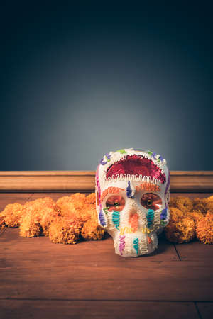 sugar skull used for dia de los muertos celebration in a grey background with cempasuchil flowers