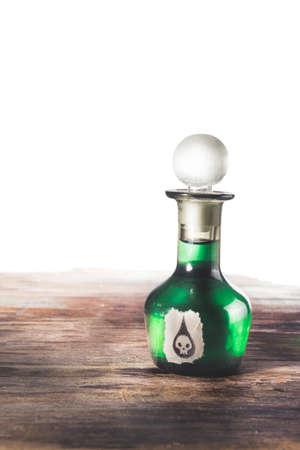poison bottle: poison bottle on a wood surface isolated on white