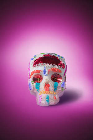 mexican folklore: High contrast image of sugar skull used for dia de los muertos celebration in a pink background