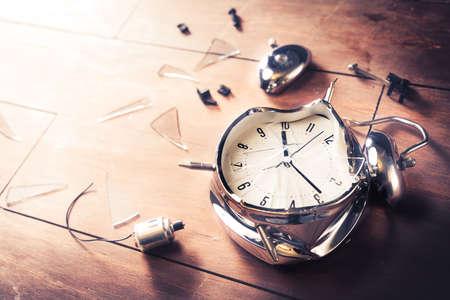 molesto: reloj despertador destruida en un fondo de madera Foto de archivo