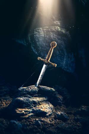 エクスカリバー、光と石の剣、暗い洞窟に塵のスペックの高コントラスト画像 写真素材