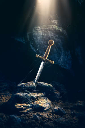 High contrast image of Excalibur, sword in the stone with light rays and dust specs in a dark cave