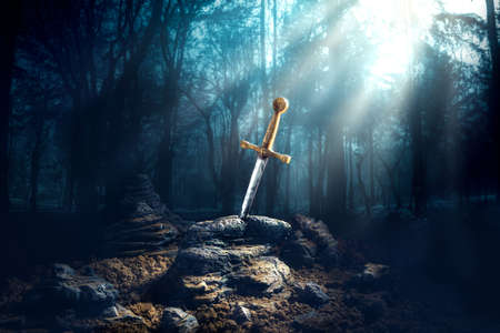 High contrast image of Excalibur, sword in the stone with light rays and dust specs in a dark forest Stock Photo - 64141939