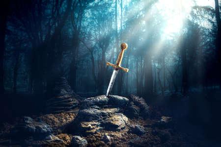 Wysoki kontrast obrazu Excalibur, miecz w kamieniu z promieniami światła i specyfikacji pyłu w ciemnym lesie