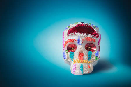 died: High contrast image of sugar skull used for dia de los muertos celebration in a blue background