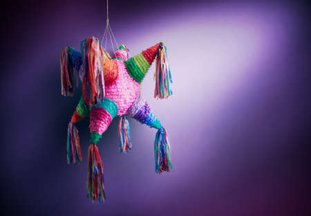 pinata: Colorful mexican pinata used in birthdays on a purple background