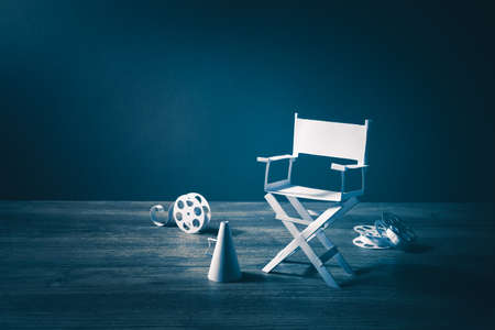 filmmaker: high contrast vintage image of Director chair and several movie items made from paper on a wood surface