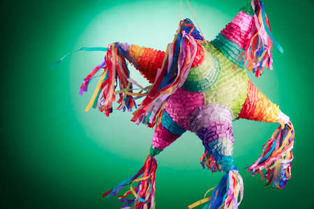 Colorful mexican pinata used in birthdays on green background
