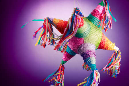 Colorful mexican pinata used in birthdays on a purple background