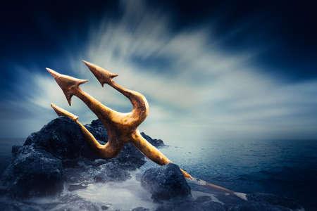 neptuno: Imgae alto contraste de reposo tridente de Poseidón en unas rocas junto al mar