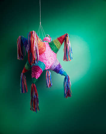 ata: Colorful mexican pinata used in birthdays on green background
