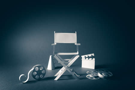 directors cut: high contrast vintage image of Director chair and several movie items made from paper on a wood surface