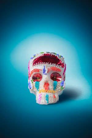 High contrast image of sugar skull used for dia de los muertos celebration in a blue background