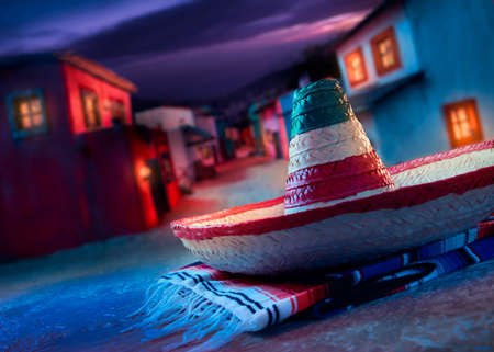 Mexican hat sombrero on a serape in a mexican town at night
