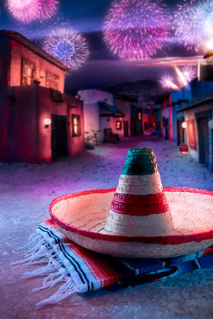 Mexican hat sombrero on a serape in a mexican village at twilight and fireworks